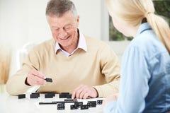 Hogere Mens het Spelen Domino's met Tienerkleindochter Stock Afbeeldingen