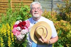 Hogere mens met bos van bloemen Stock Foto's