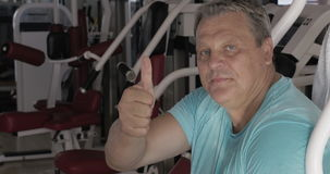 Hogere mens met duim omhoog en glimlach tussen oefeningen in gymnastiek stock video