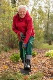Hogere mens met een spade in tuin Stock Afbeeldingen