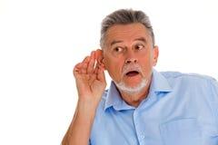 Hogere mens met hand aan oor het luisteren Stock Foto