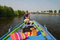 Hogere mens met hond in boot Stock Foto's
