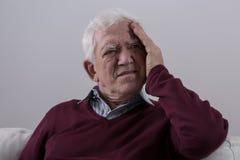 Hogere mens met hoofdpijn Stock Foto's
