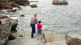 Hogere mens met kind die hengel werpen aan het overzees stock footage