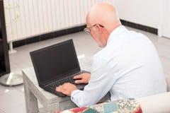 Hogere mens met notitieboekjezitting in bank Royalty-vrije Stock Foto