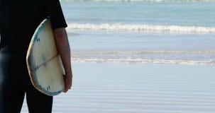Hogere mens met surfplank die zich op strand bevinden stock footage