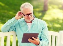 Hogere mens met tabletpc bij de zomerpark royalty-vrije stock afbeeldingen