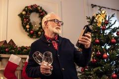 Hogere mens met wijn bij christmastime royalty-vrije stock afbeelding