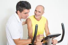 Hogere mens op fiets in gymnastiek royalty-vrije stock afbeeldingen