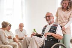Hogere mens op rolstoel met nuttige verzorger ondersteunend hem stock foto's