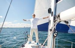 Hogere mens op zeilboot of jacht die in overzees varen stock fotografie