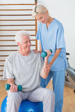 Hogere mens opleiding met zijn therapeut Stock Fotografie