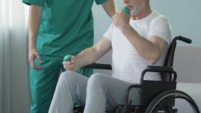 Hogere mens in rolstoel verbuigingswapens met domoren, bijgestaan door verpleegster, rehab stock footage