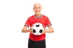 Hogere mens in rood Jersey die een voetbal houden Royalty-vrije Stock Afbeelding
