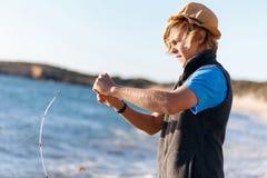 Hogere mens visserij op zee kant royalty-vrije stock afbeeldingen
