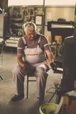 Hogere mens in workshop De mens loog brand in workshop stock fotografie