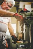 Hogere mens in workshop Timmerman die in garage werken stock foto's