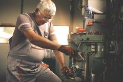 Hogere mens in workshop Timmerman die in garage werken stock fotografie