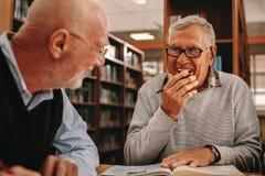Hogere mensen die in een bibliotheek en het bestuderen zitten royalty-vrije stock afbeeldingen