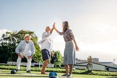 Hogere mensen die een spel van boules in een park spelen royalty-vrije stock fotografie