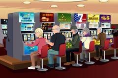 Hogere mensen die gokautomaten in het casino spelen Stock Fotografie