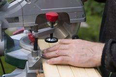 Hogere mensen die houten materialen met roterende zaag voorbereiden stock afbeelding