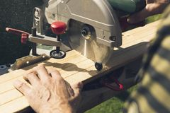 Hogere mensen die houten materialen met roterende zaag voorbereiden stock afbeeldingen