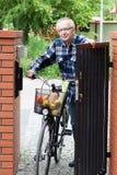 Hogere mensen duwende fiets door de poort Stock Foto's