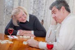Hogere mensen in speel de dominospel van het pensioneringshuis Royalty-vrije Stock Foto's