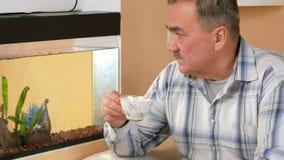 Hogere mensensnor die met een kop van hete drank rusten Hij zit op de laag dichtbij het aquarium en het bekijken vissen stock videobeelden