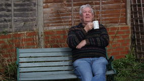 Hogere mensenzitting buiten het drinken van thee of koffie stock footage
