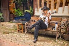 Hogere mensenzitting op bank het spelen banjo royalty-vrije stock afbeelding