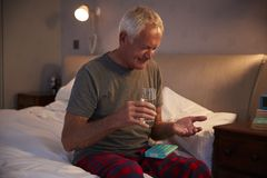 Hogere Mensenzitting op Bed die thuis Medicijn nemen royalty-vrije stock afbeeldingen