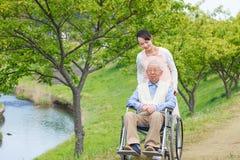 Hogere mensenzitting op een rolstoel met verzorger Stock Afbeelding