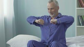 Hogere mensenzitting op rand van bed en geeuw, gelukkige ochtend, volledig van energie stock video