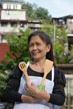 Hogere Minderheids Vrouwelijke Cook And Happiness Wearing Schort met Werktuigen royalty-vrije stock foto