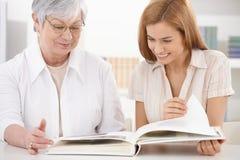 Hogere moeder en dochter die fotoalbum bekijken Stock Afbeeldingen