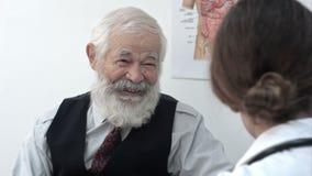 Hogere oude mens die aan arts bij het ziekenhuis spreken stock video
