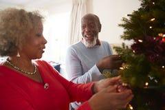 Hogere Paar Hangende Decoratie op Kerstboom thuis samen royalty-vrije stock foto's
