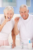Hogere paar het borstelen tanden stock afbeeldingen