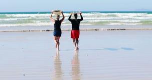 Hogere paar het dragen surfplankoverheadkosten terwijl het lopen naar het overzees stock footage