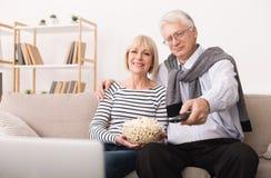 Hogere paar het letten op televisie en het eten van popcorn royalty-vrije stock afbeelding
