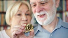 Hogere paarholding en het bekijken cryptocurrency bitcoin Glanzend virtueel geld van online handel stock footage