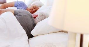 Hogere paarslaap op bed in slaapkamer stock videobeelden