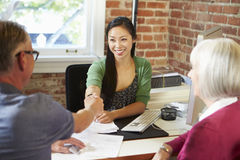 Hogere Paarvergadering met Financiële Adviseur in Bureau Stock Foto's