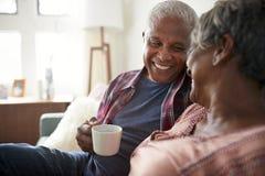 Hogere Paarzitting op de Hete Drank van Sofa At Home Relaxing With stock fotografie