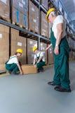 Hogere pakhuisarbeider die jonge medewerkers controleren stock foto's