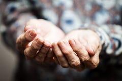 Hogere persoonshanden die voor voedsel of hulp bedelen stock fotografie