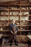 Hogere pottenbakker in schort die zich tegen planken met aardewerkgoederen op workshop bevinden stock foto's