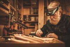 Hogere restaurateur die met antiek decorelement werken in zijn workshop Royalty-vrije Stock Fotografie